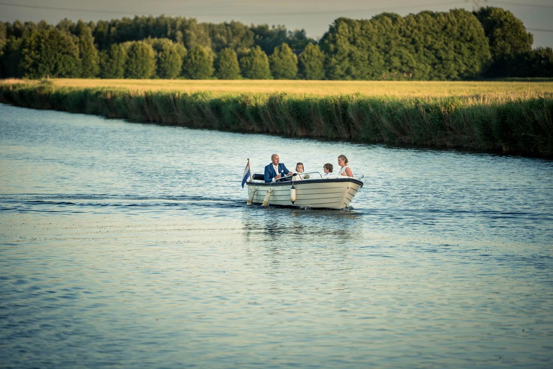 In het huwelijksbootje bij Gastel Sfeer aankomst van het bruidspaar in West Brabant door Caroline bruidsfotograaf bij Cfoto