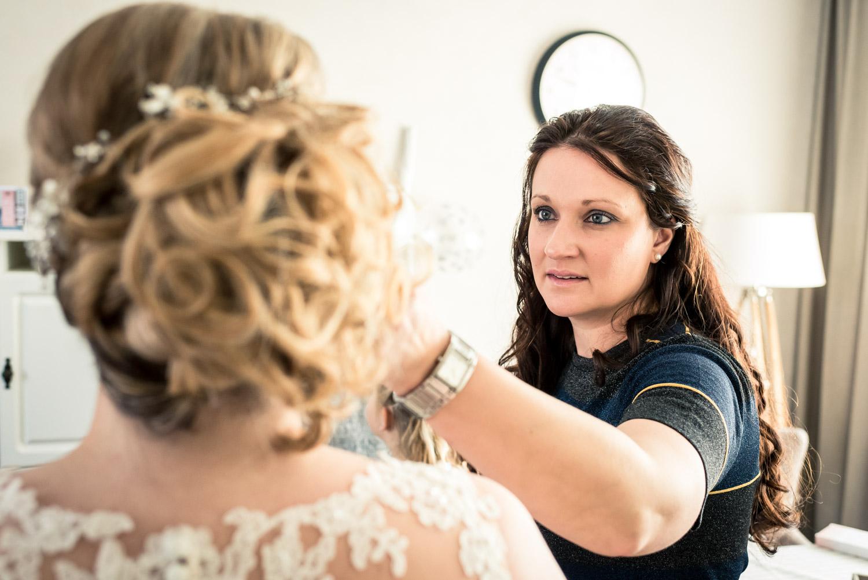 De zus helpt bij het aankleden van de bruid in Steenbergen