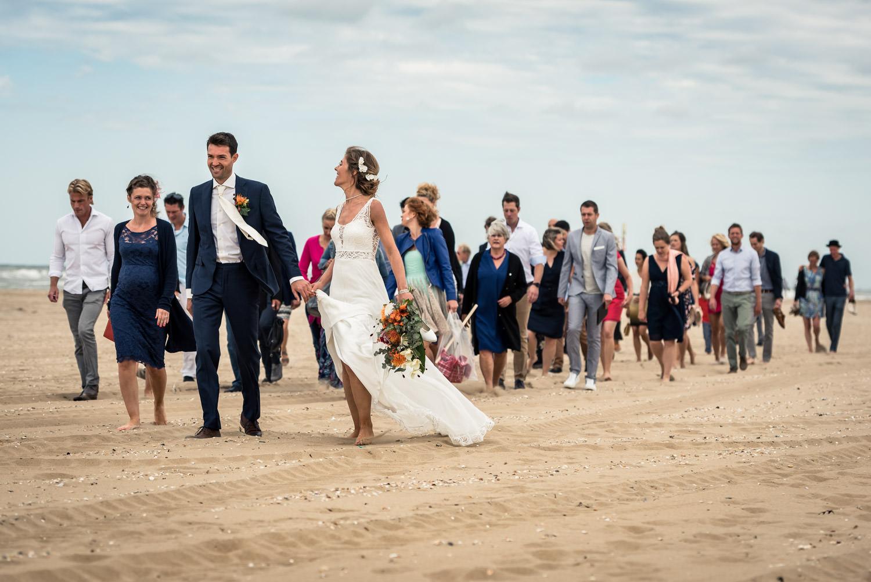 het bruidspaar loopt over het strand met het hele gezelschap, br