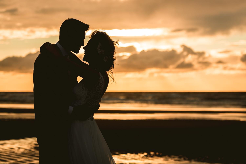 spontaan moment aan het strand bij zonsondergang tijdens bruidsr