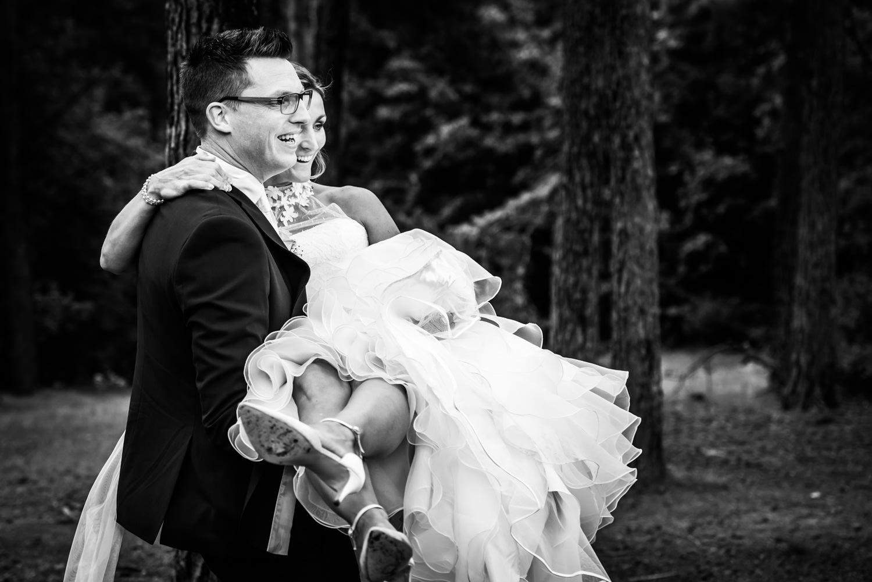 De bruidegom tilt de bruid om op haar over de sloot te dragen.
