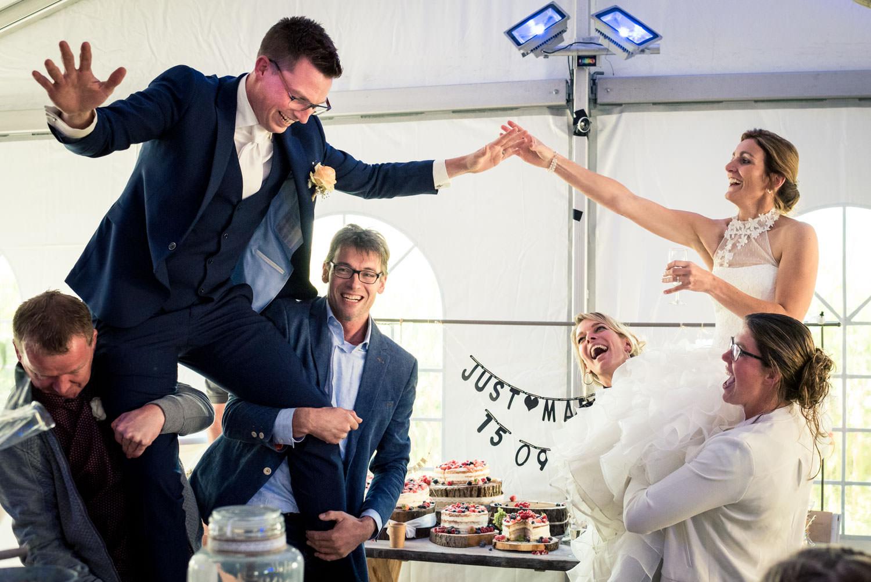 Het bruidspaar wordt omhoog gehouden door vrienden tijdens de tr