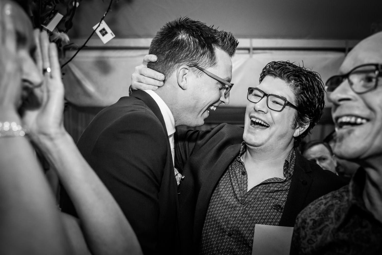 Tijdens het trouwfeest moment felicitatie van bruidegom en een g