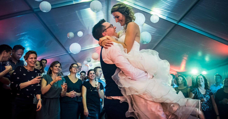 Trouwfotografie bruidspaar met lift bruid tijdens het trouwfeest