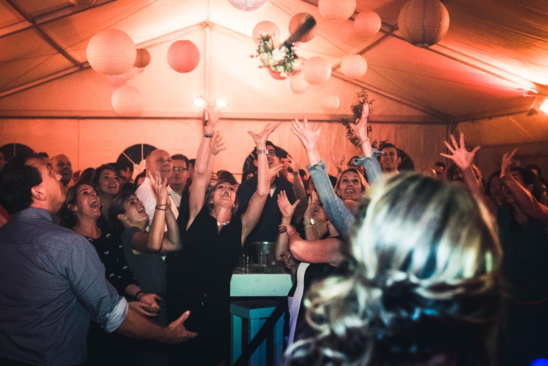 de gasten vangen het boeket tijdens het trouwfeest.