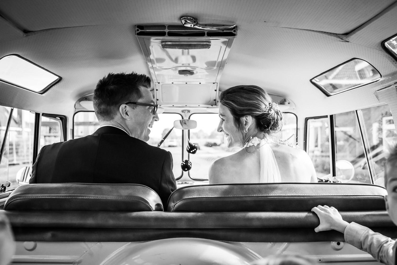 bruidspaar zit in een volkswagenbusje, bruidspaar op weg naar br