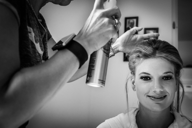 bruid tijdens getting ready, er wordt haarlak gespoten, een echt
