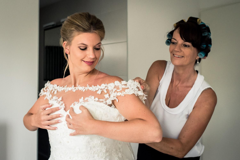 moeder van de bruid helpt met aankleden en aantrekken van de bru