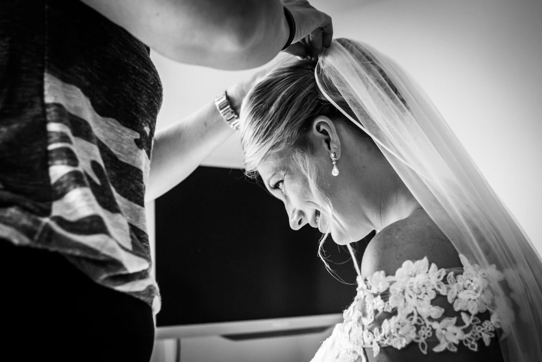 hier wordt de sluier bij de bruid aangedaan, door hem in het haa