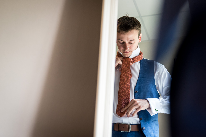 groom is looking tot his tie in the mirror