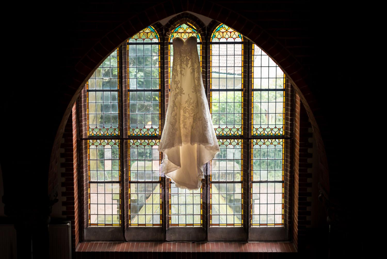 De bruidjurk hangt mooi in het raam klaar voor het grote moment