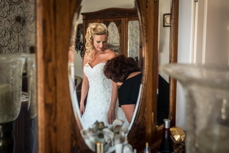 gereedmaken foto door de spiegel, jurk aantrekken samen met moed