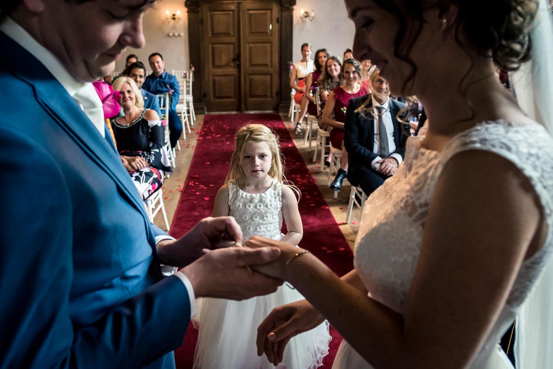 bruidsmeisje geeft de ringen tijdens de ceremonie op kasteel dus