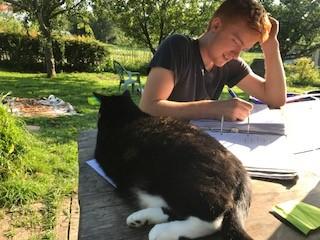Ruben doing homework with the farm cat.jpg
