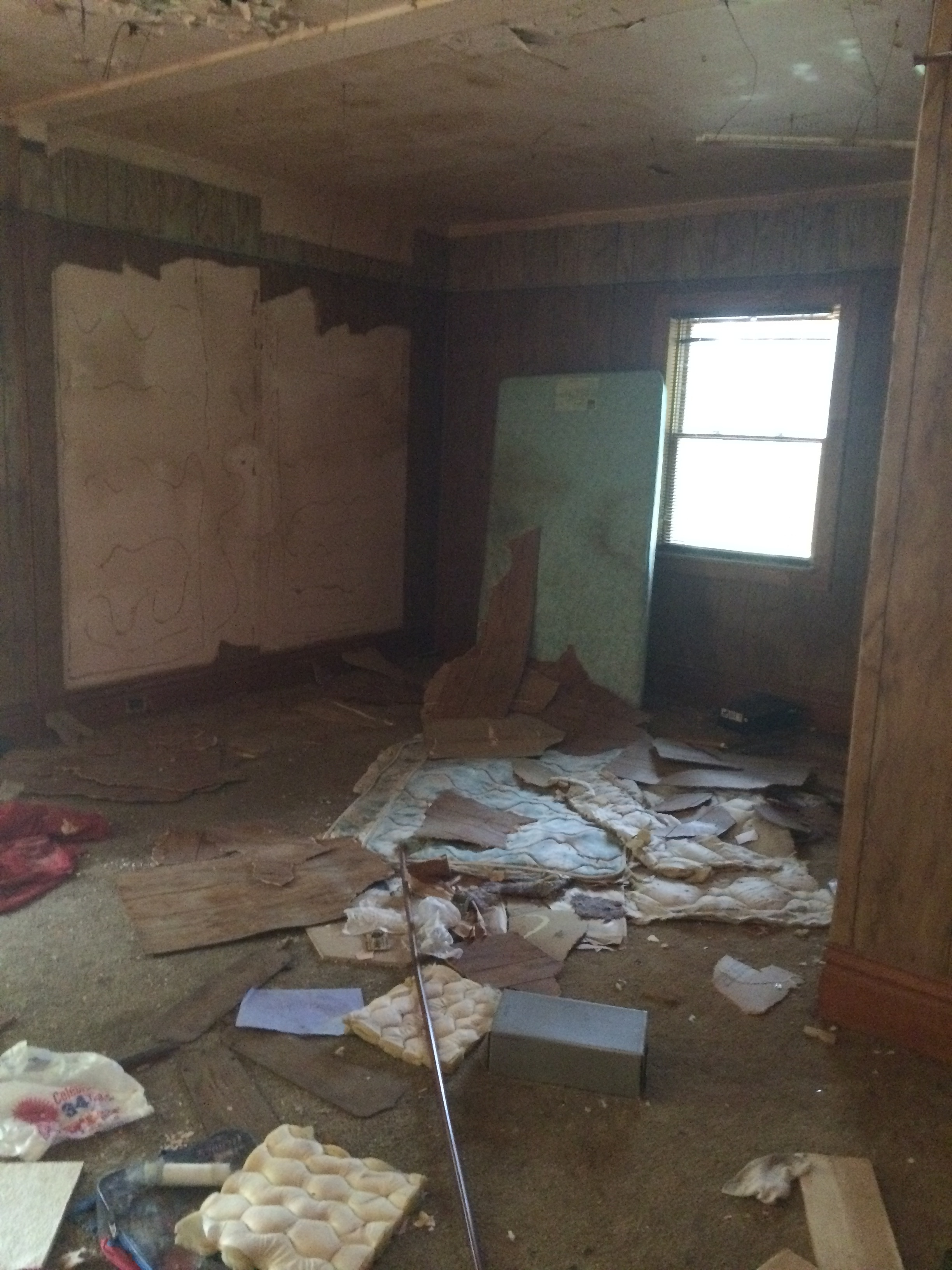Before: Damaged paneling wall, living room, one small window