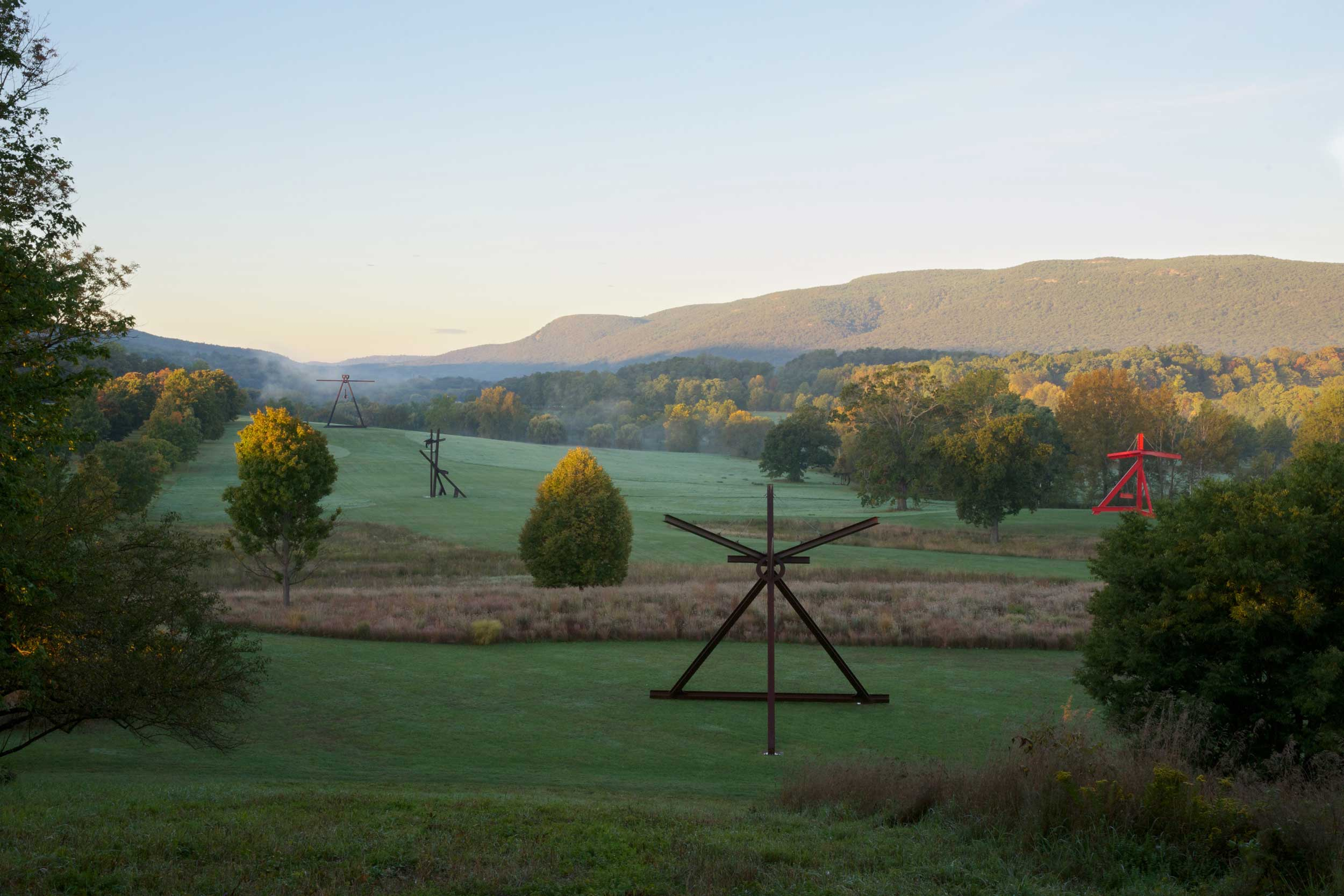 View of the South Fields, all works by Mark di Suvero. Background:  Pyramidian , 1987/1998;  Jeanne , 2014–2015;  Mon Père, Mon Père , 1973–75;  Mother Peace , 1969–70. Below: Alexander Liberman,  Iliad , 1974-1976 (left); Mark di Suvero,  Frog Legs , 2002,  Mozart's Birthday , 1989, and  Neruda's Gate , 2005 (right). Photo credit: Jerry L. Thompson.