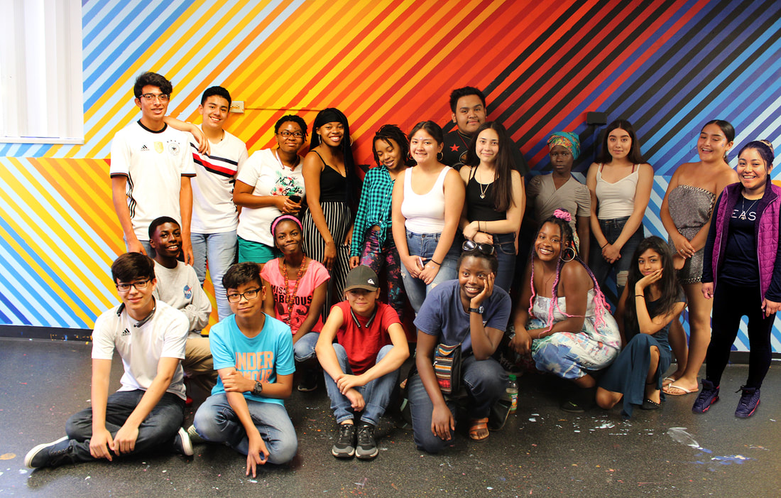 One of several YEA Summer Intern cohorts, posing for the camera in front of a mural they helped create and paint, with member's of Denver arts organization, Birdseed Collective.