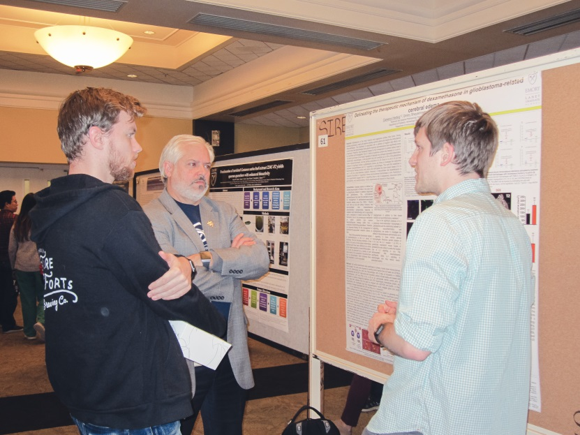 Dr. Nael McCarty discussing posters with students.