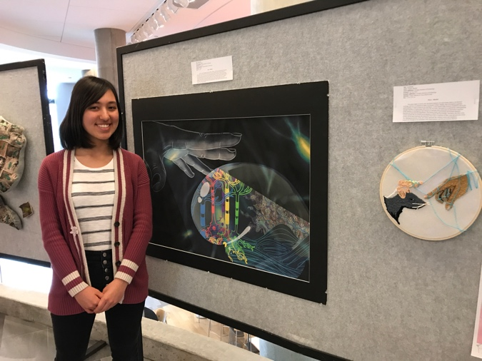 Natalie Mueller shows off her artwork based on neuroscience research from the Dyer lab.