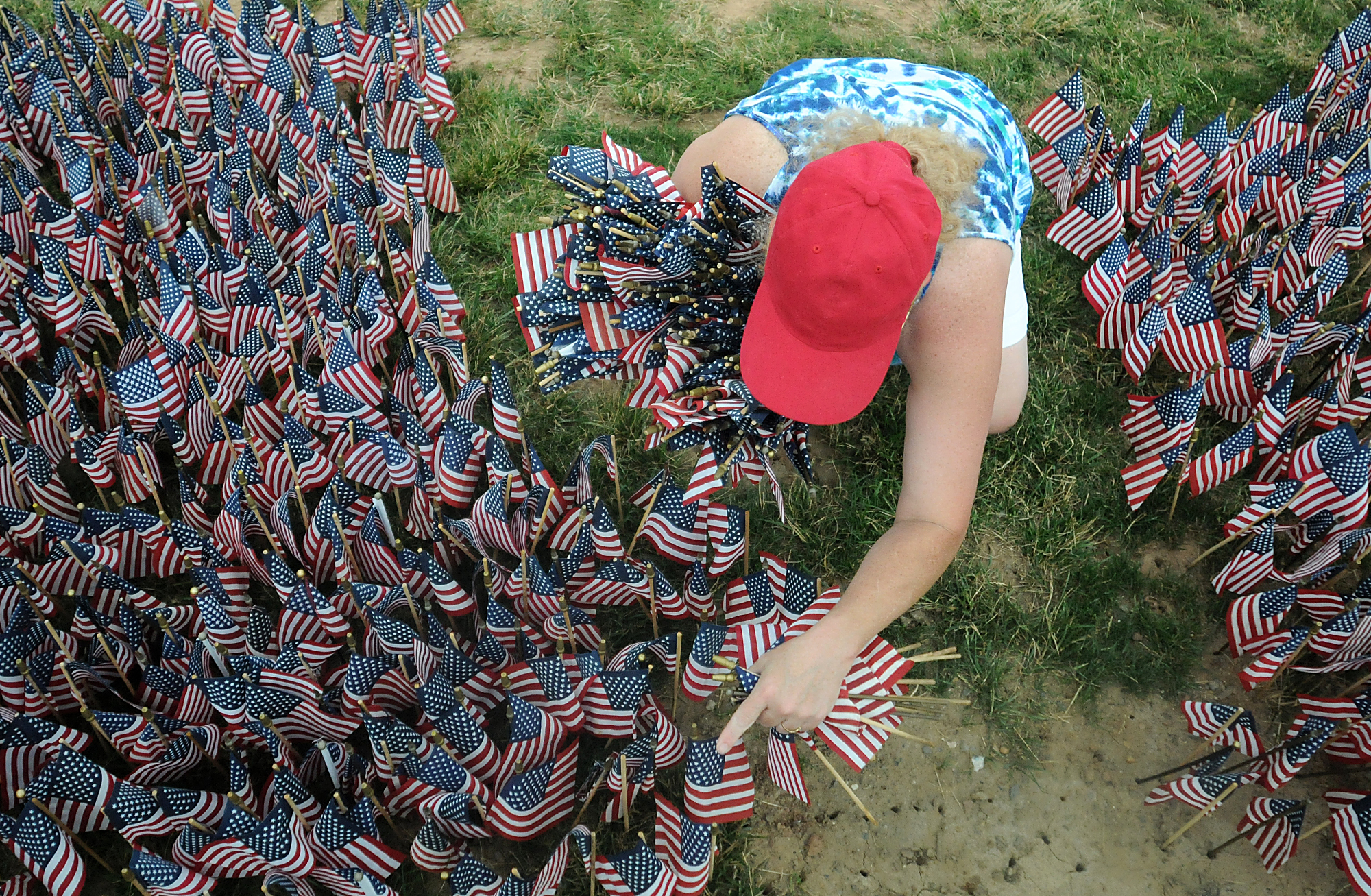 Donna Donohue, a friend of Treasurer Jesse Hill, unplants and collects flags following the Delaware Valley Vietnam Veterans 30th annual Donald W. Jones Flag Memorial for Flag Day at Falls Township Community Park on Sunday, June 14, 2015. 65,000 flags are placed in the ground for the memorial, which represents each American killed or Missing In Action during the Vietnam War.