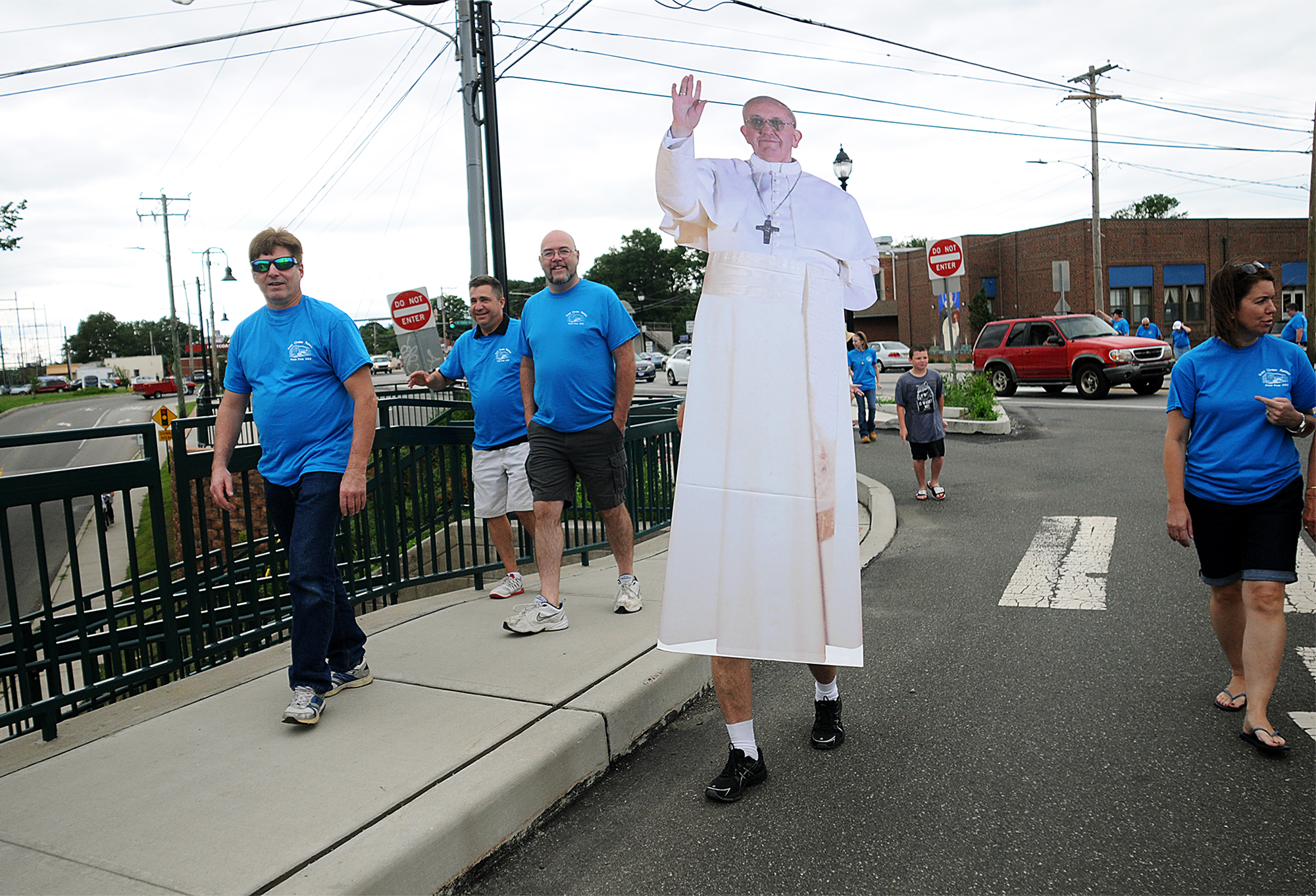 Parishioners from St. Thomas Aquinas Church in Croydon walk with fellow parishioner Tony Cinkutis, 75, as he carries a cardboard cutout of Pope Francis to the train station across the street from their church on Sunday, June 28, 2015. The Croydon train station was a stop on the Trenton line for the World Meeting of Families in September.