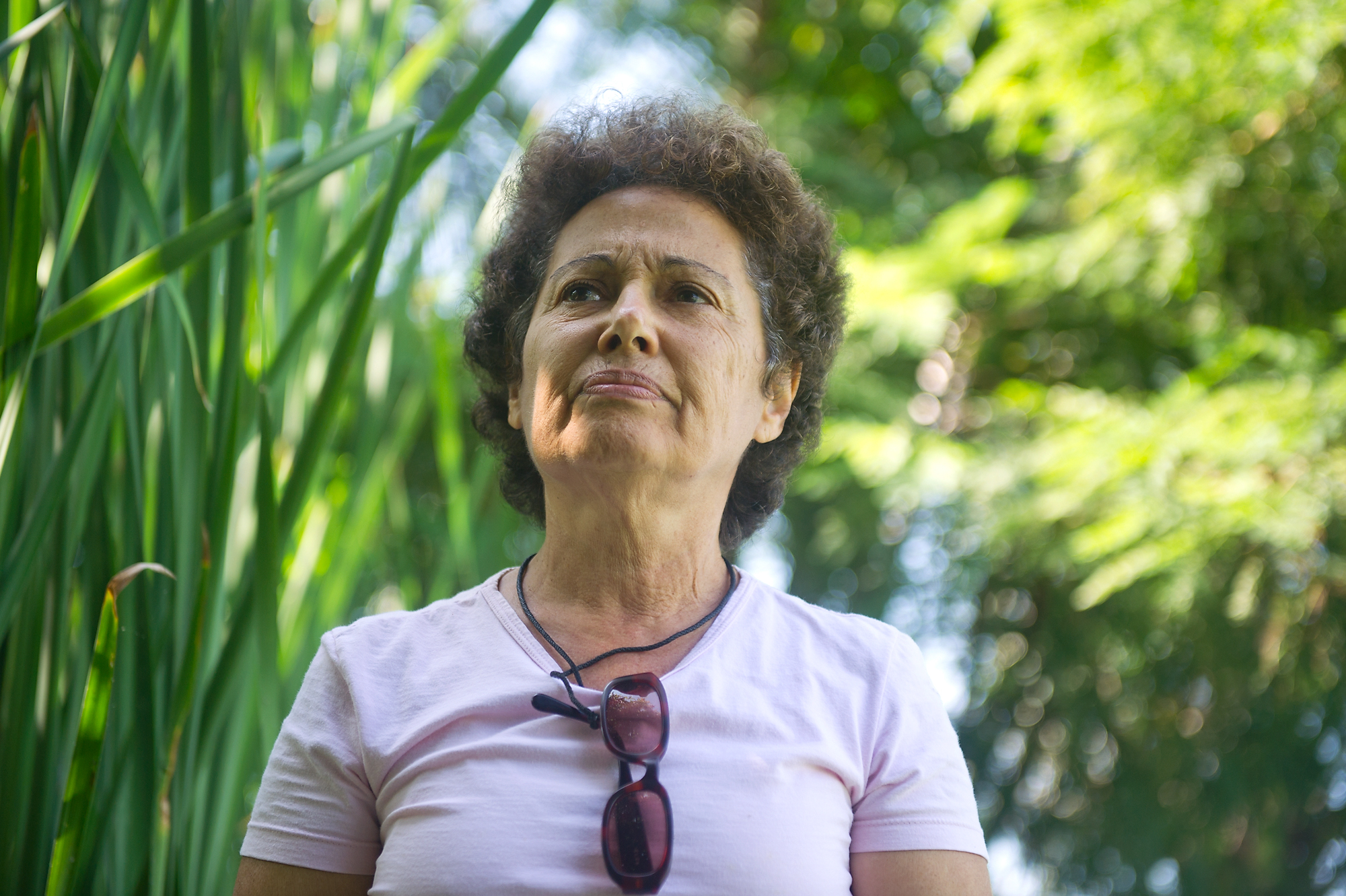 Inalva Mendes Brito, 65, takes a moment in her backyard in Vila Autodromo by the lagoon, which is heavily polluted.