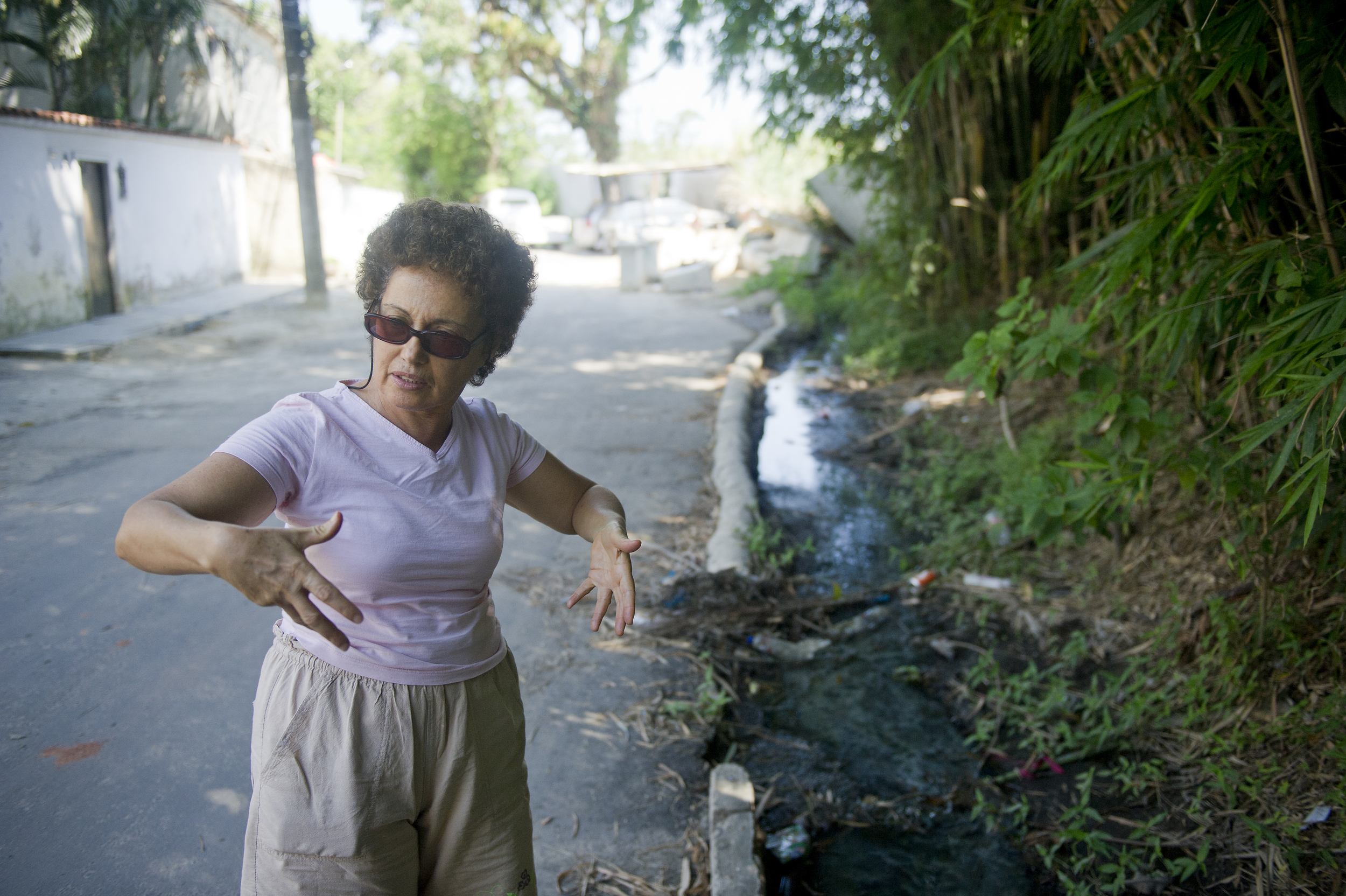 Brito describes the differences between this town and hers. She stands at the edge of an open sewer that runs through the town next to the area where the government is trying to relocate Vila Autodromo.