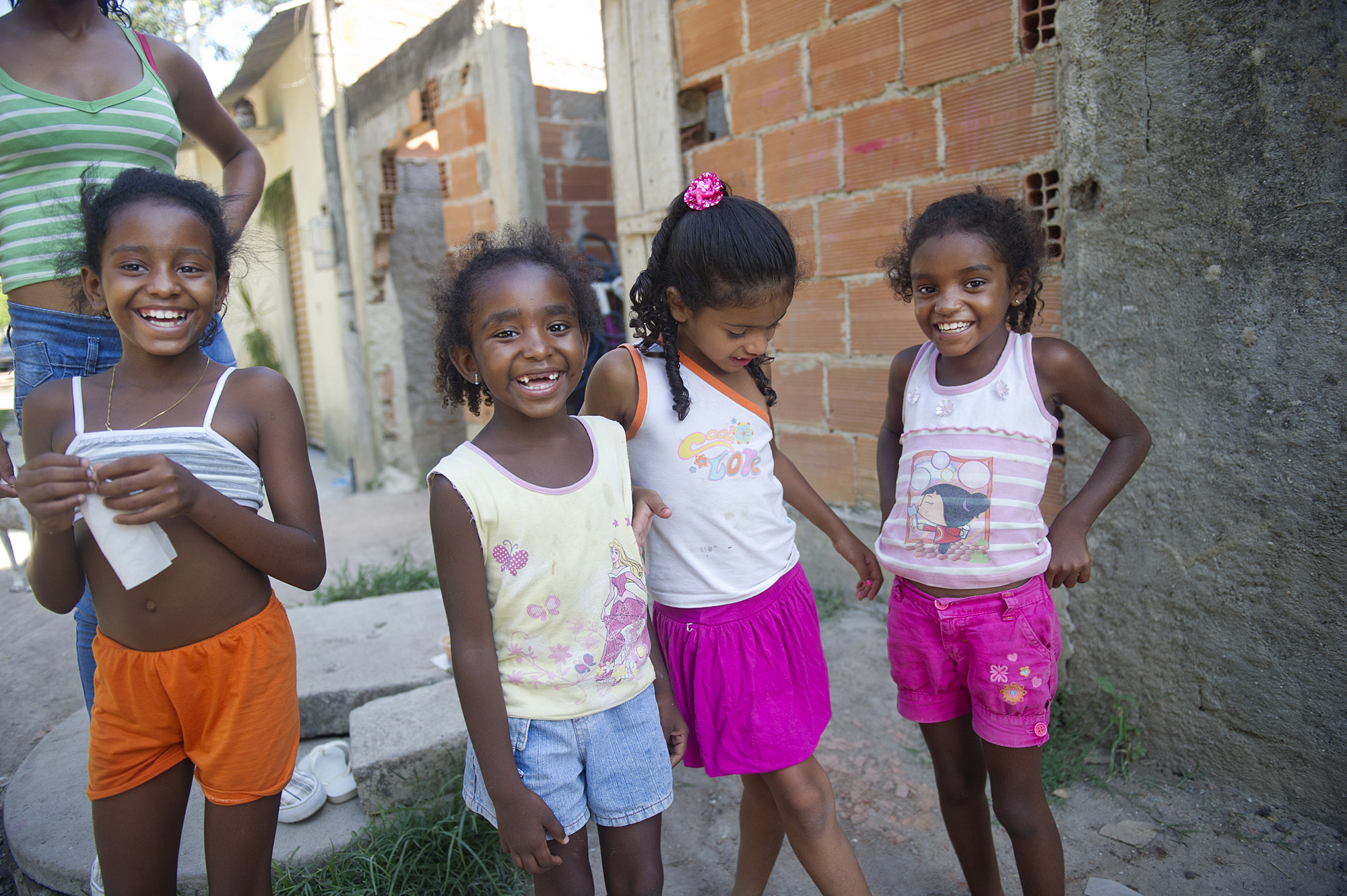 Sisters Thamires, 10, Joyce, 6, Raissa, 7, and cousin Maria (pink skirt), 6, giggle during a game of hopscotch in Vila Autodromo in Rio de Janeiro, Brazil, a favela that the government is trying to evictbecause it lays on Olympic planning ground. The city is set to host the 2016 Olympic games.