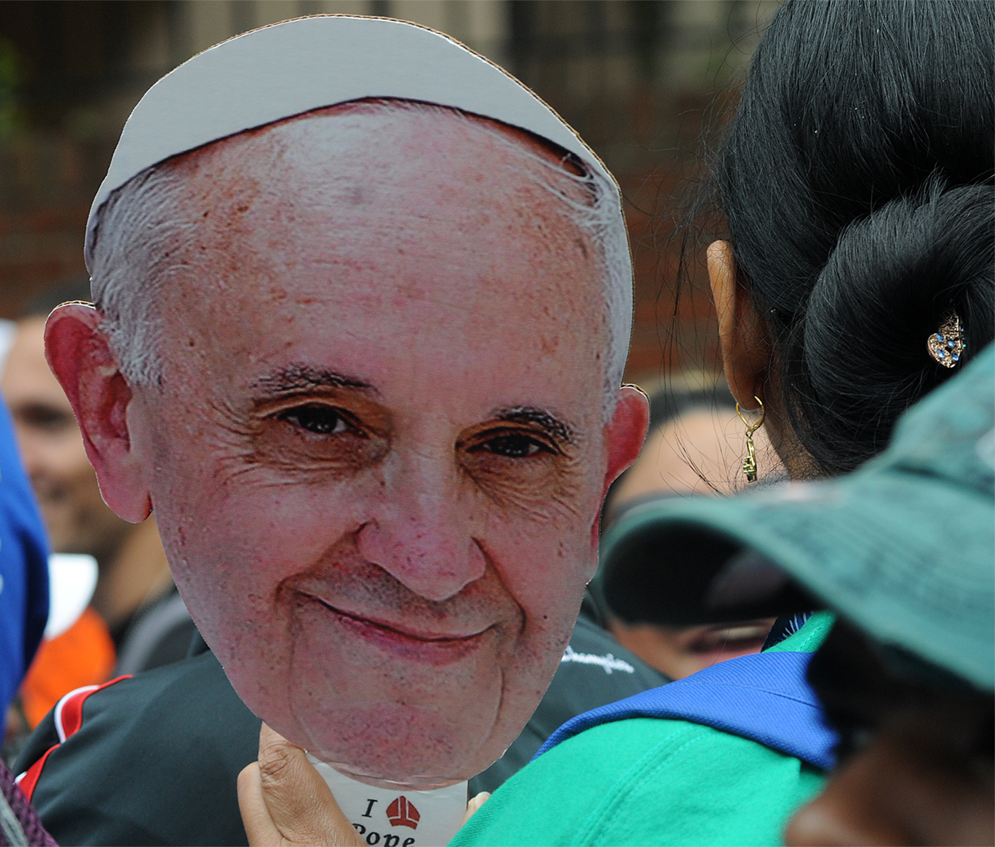 A woman holds a Pope Francis cardboard cutout while waiting to see Pope Francis' Mass on the Ben Franklin Parkway on September 27, 2015. Lines were multiple hours-long waits with no bathrooms or handicap entrances along the route.