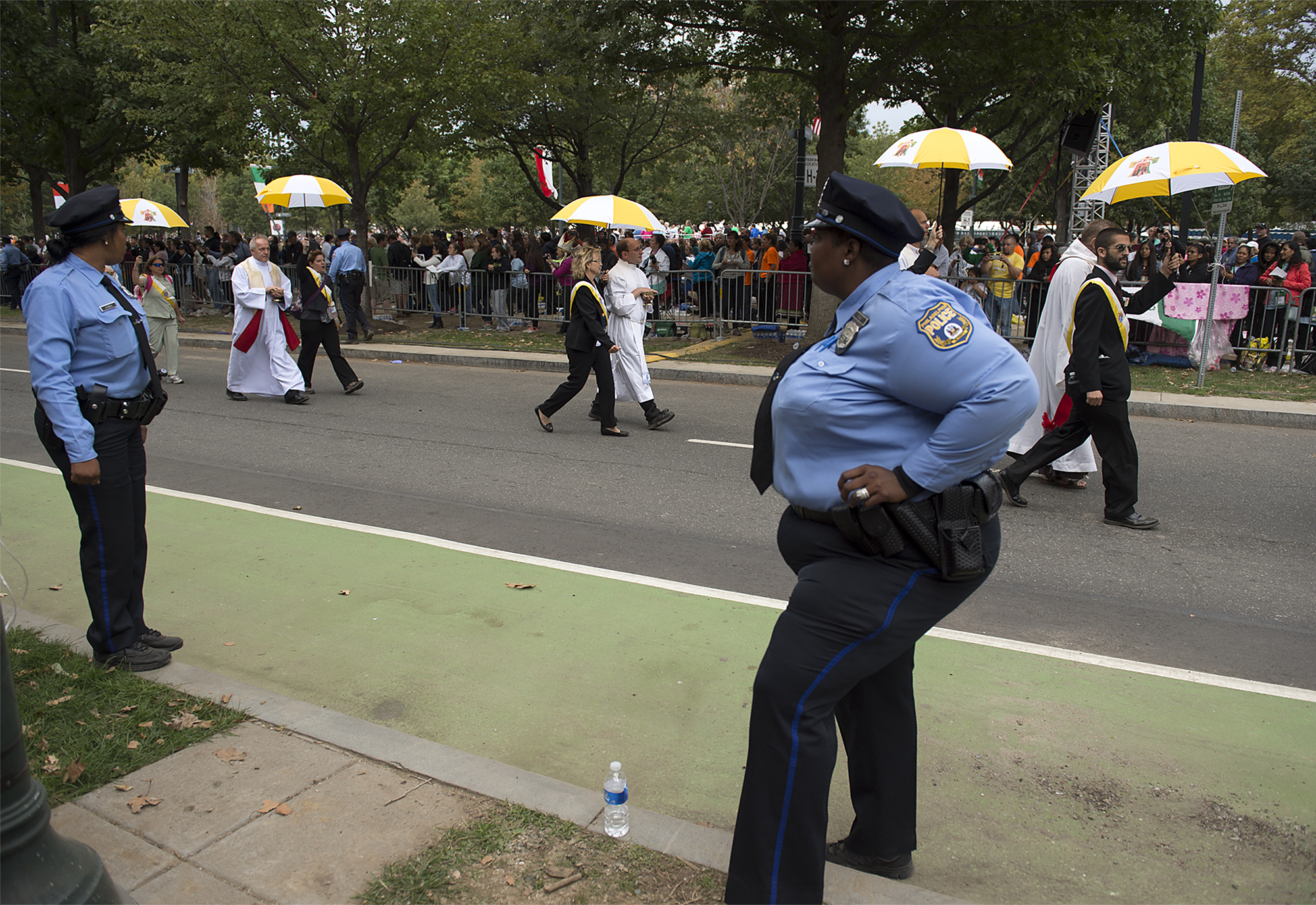 Philadelphia Police Officers watch as priests are escorted throughout the parkway to give communion as Pope Francis holds Mass on the Ben Franklin Parkway on September 27, 2015.