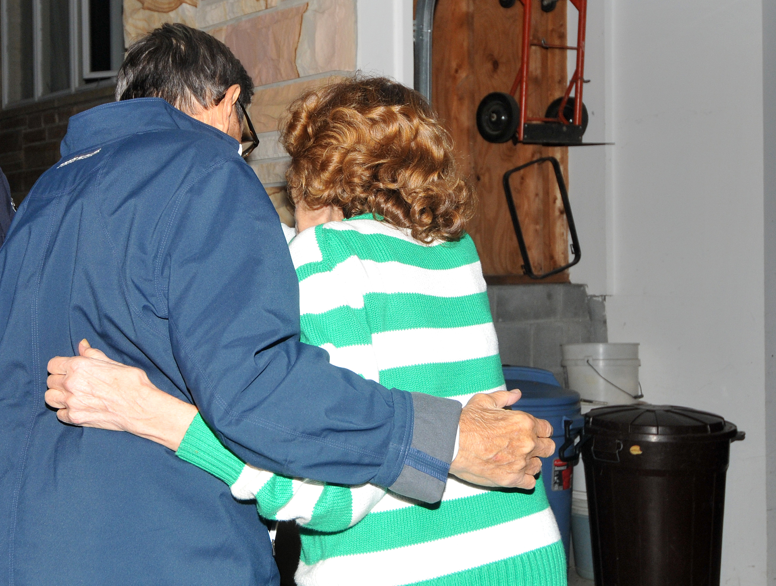Head coach Joe Paterno and wife Sue embrace as they walk into their home in State College on Tuesday night. A crowd of around 300 students gathered in support of Paterno.
