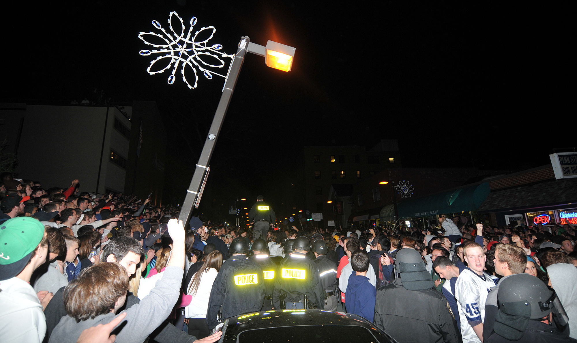 A policeman (center) walks on top of a car to use pepper spray on a rioter on Beaver Avenue during the riots on Wednesday night. The lightpole was also being torn down by rioters.