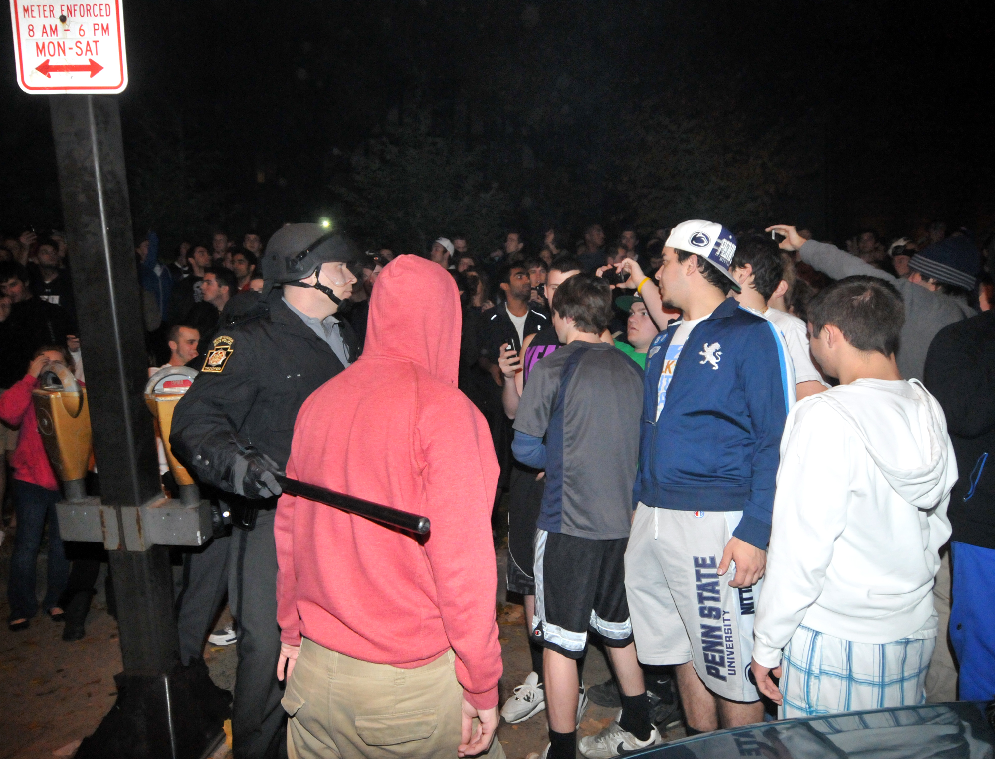 A student is ushered off of the street during the riots in Beaver Canyon in downtown State College on Wednesday night after the riots got violent.