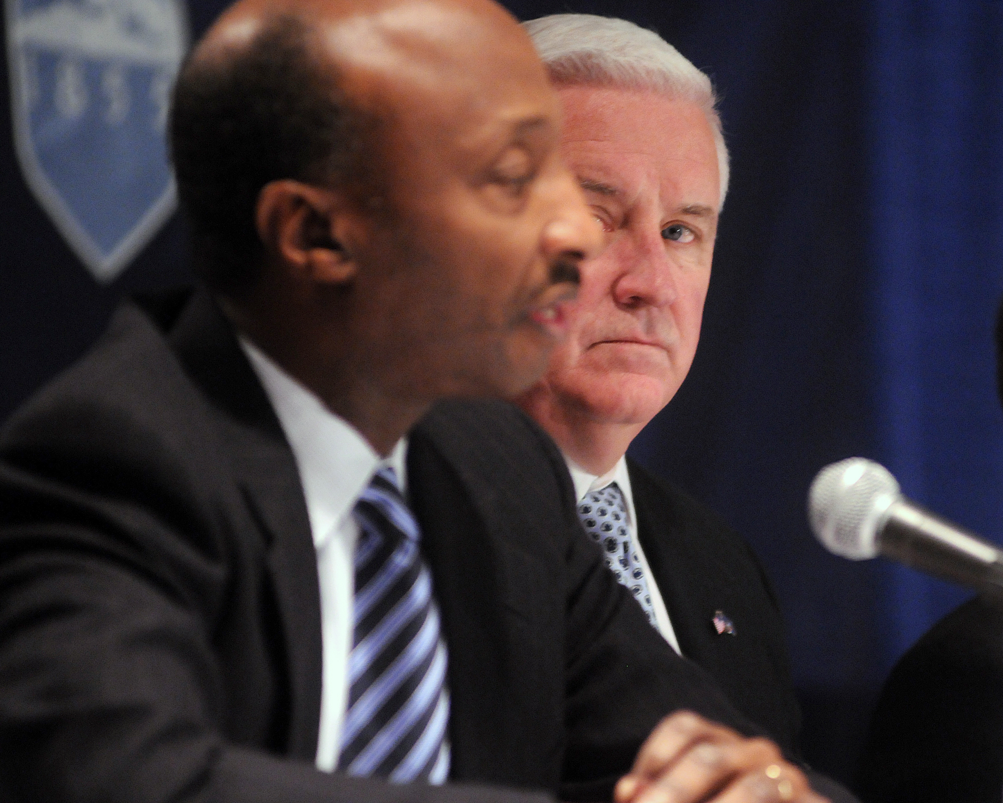 Governor Tom Corbett, right, watches as Kenneth Frazier, chairman of the investigative committee, speak to media following the Board of Trustees meeting on Friday, Jan. 20, 2012 at the Nittany Lion Inn.