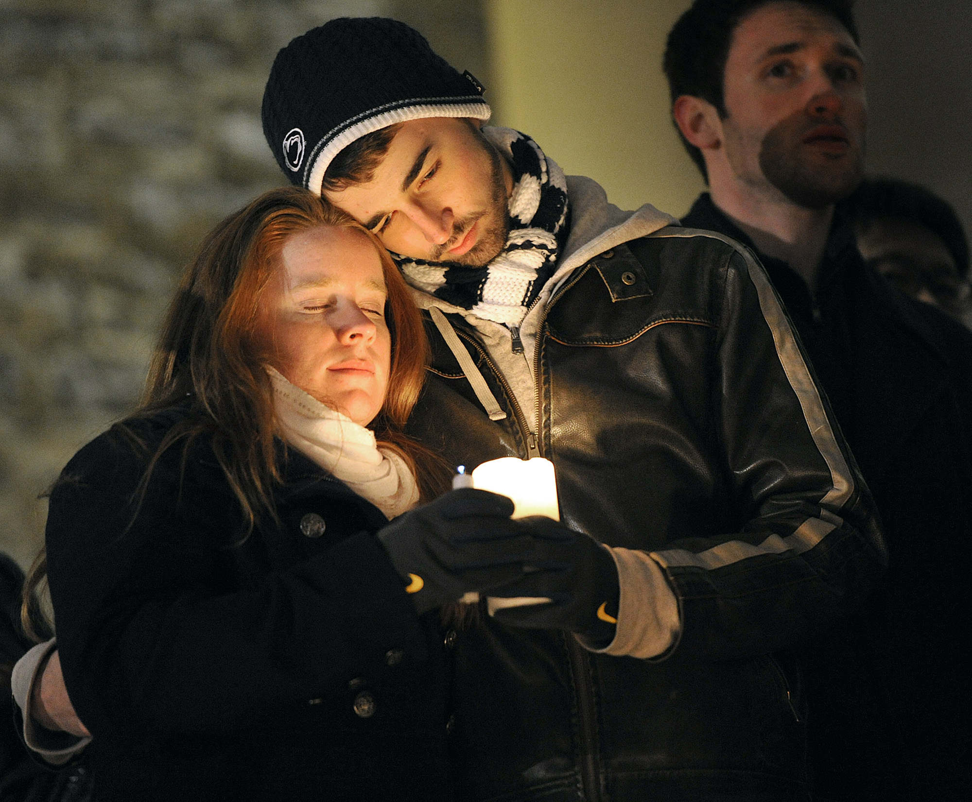 Andrew Adamietz (sophomore-secondary english education) and Katie Knobloch (senior-elementary education), both members of Blue in the Face, embrace on the stairs of Old Main on Sunday night during the candlelit vigil in memorium of Joe Paterno.