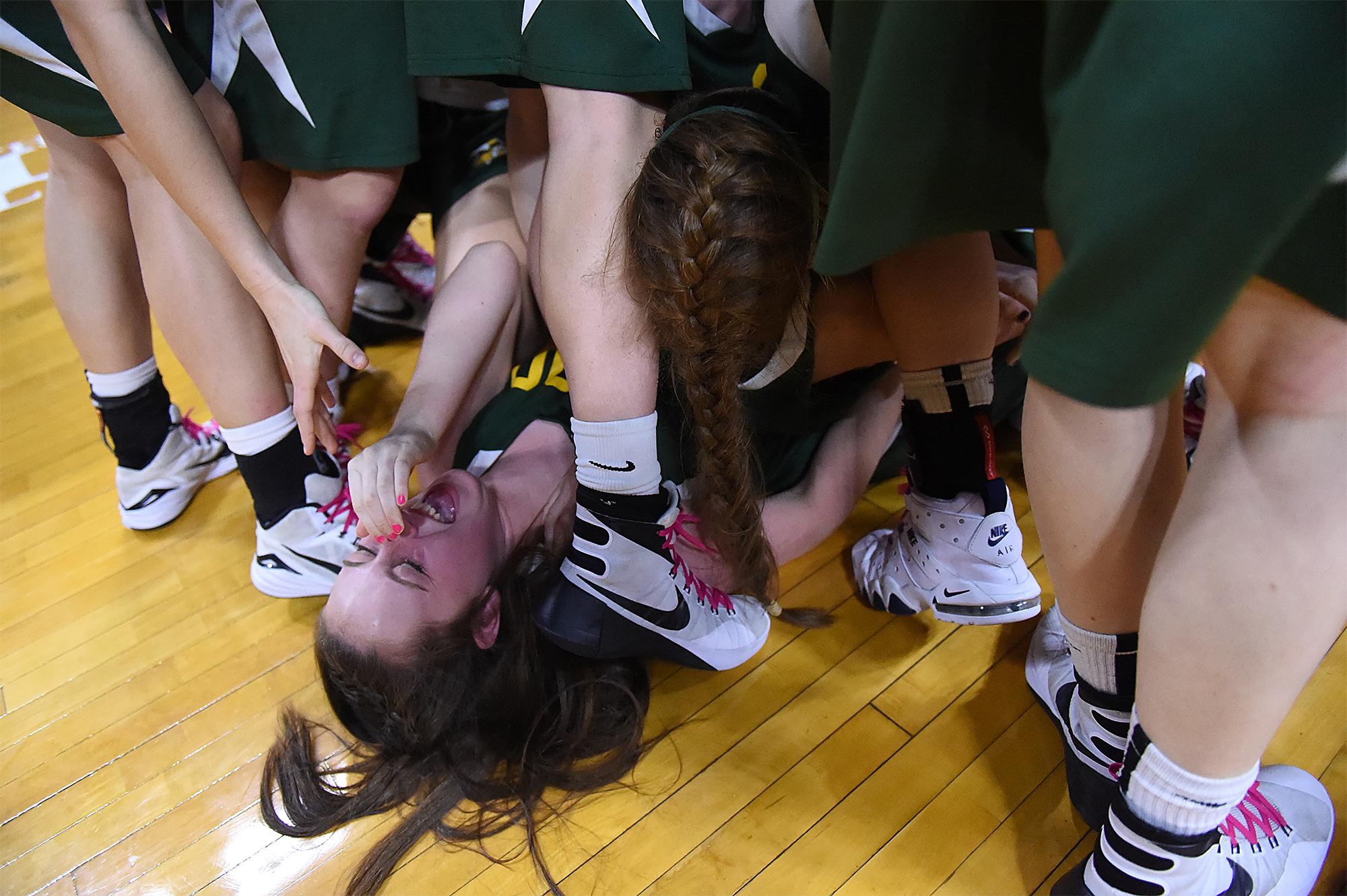 Arhcbishop Wood's Erin Morgan (22) falls to the bottom of a celebration pile following their Philadelphia Catholic League girls basketball championship game on Monday, Feb. 22, 2016 at the Palestra in Philadelphia. Archbishop Wood won the game 40-36 over Neumann-Goretti.