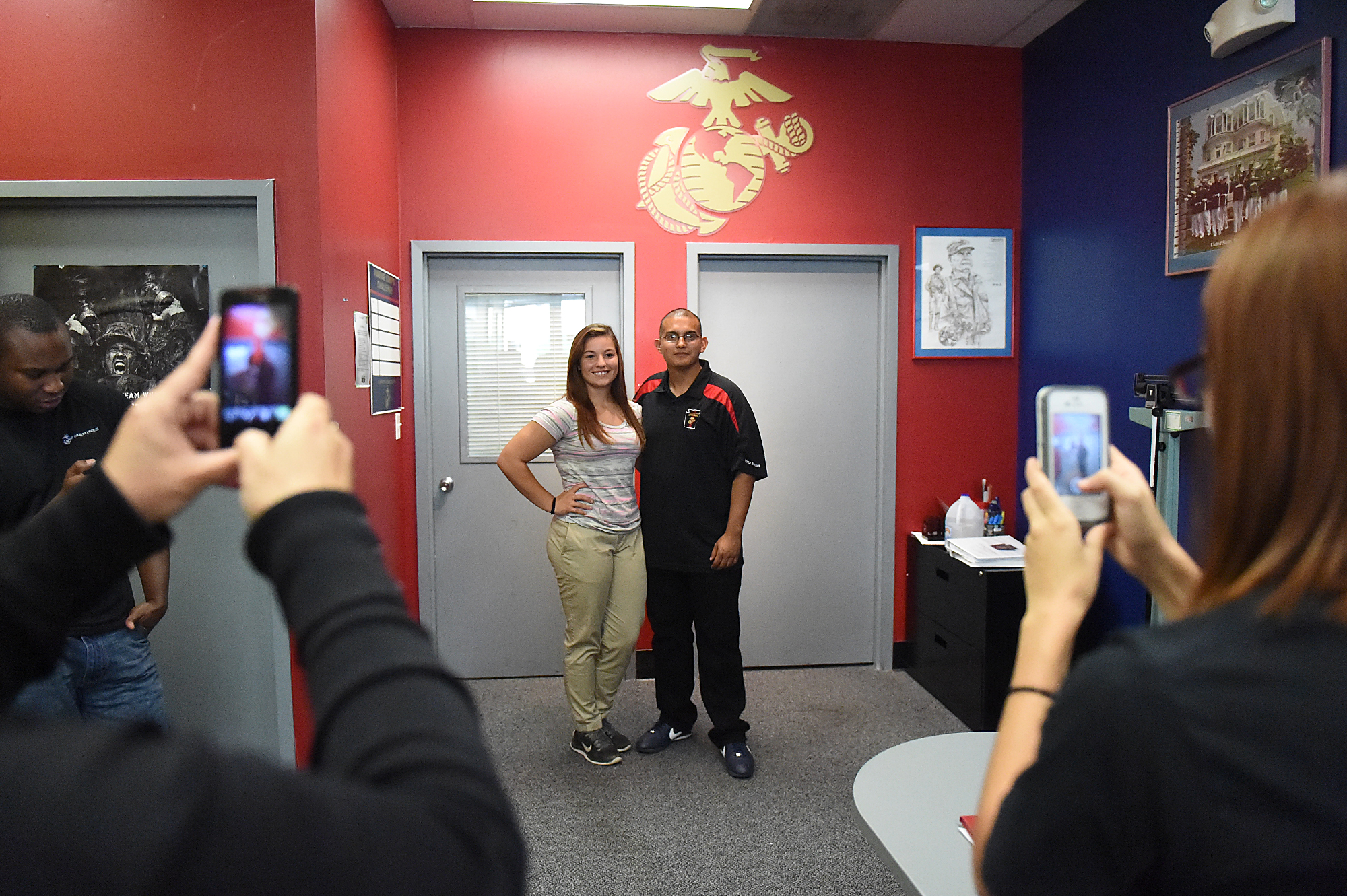 Dee Hubay poses for pictures with Sgt. Kevin Sanchez of the Marine Recruiting Sub Station Oxford Valley in Bristol Township (who has since switched stations) before leaving for boot camp at the US Marine Corps Recruiting station on Cottman Avenue in Philadelphia on Sunday, August 23, 2015.