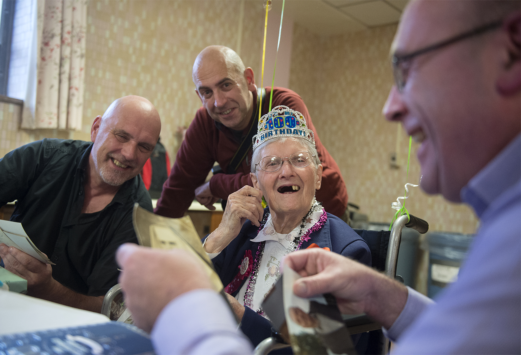 Sister Maureen Patricia Ryan laughs at an old photo of herself while surrounded by her nephews from Ireland (from left) Noel Roberts, Kevin Roberts and Ted Roberts, all sons of Ryan's sister, during a centenarian birthday celebration for her at the Motherhouse of Sisters of the Blessed Sacrament in Bensalem on Thursday, January 12, 2017.