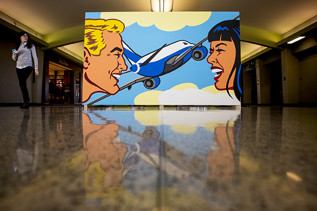 """A woman walks by one of the two """"Love is in the Air"""" murals in Concourse B of Cincinnati/Northern Kentucky International Airport Tuesday. Photo by Meg Vogel, The Cincinnati Enquirer"""