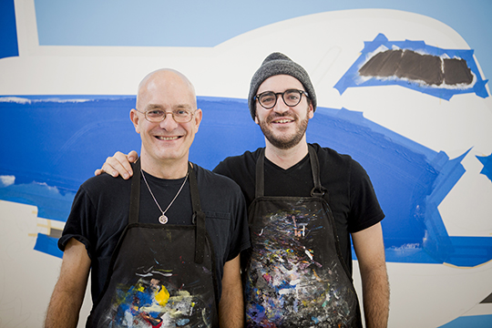 """Kevin T. and Jack Kelly pose in front of one of their """"Love is in the Air"""" murals. They're part of CVG's efforts to enhance the traveler experience. The murals will be on display in the International Arrivals Gate. Photo by Meg Vogel, The Cincinnati Enquirer"""