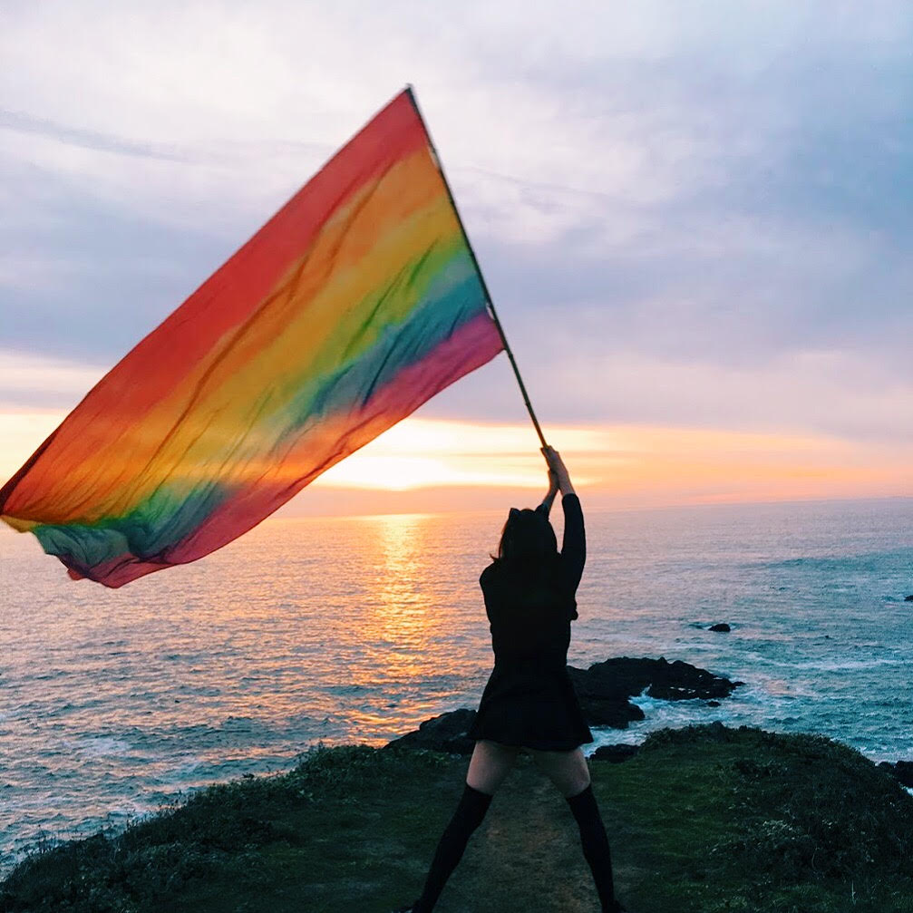 Ash triumphantly waving the famed rainbow flag.