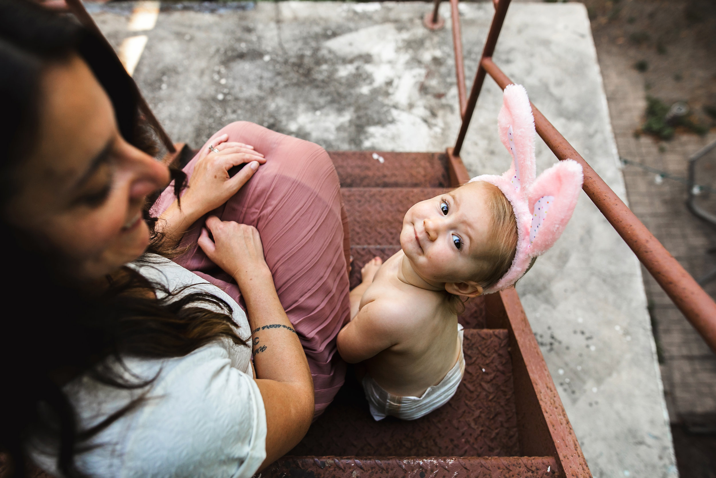 baby hangs on fire escape with mom wearing pink bunny ears 2-(ZF-0126-04493-1-016).jpg