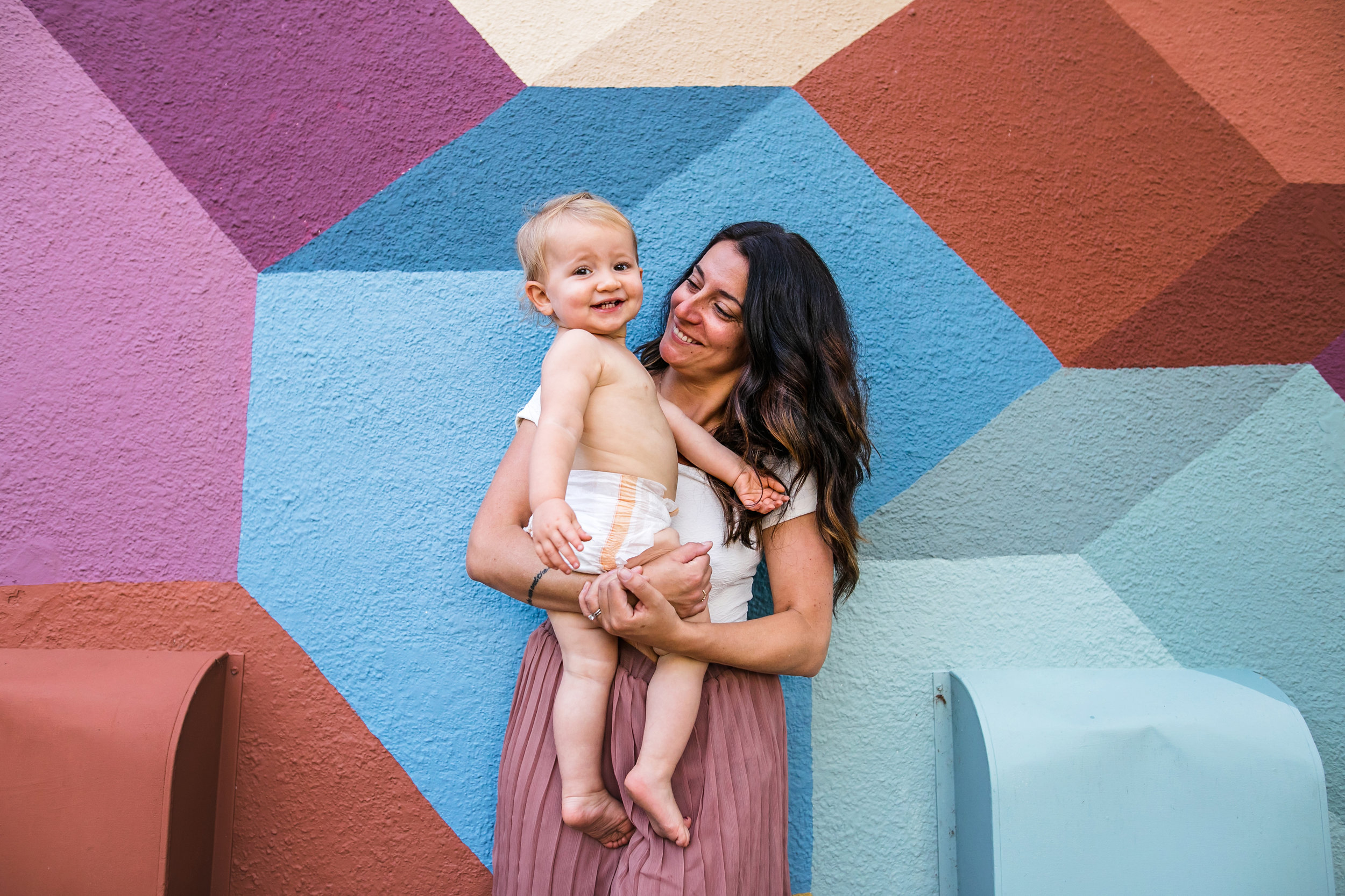 mom holds diapered baby in front of colorful wall-(ZF-0126-04493-1-037).jpg
