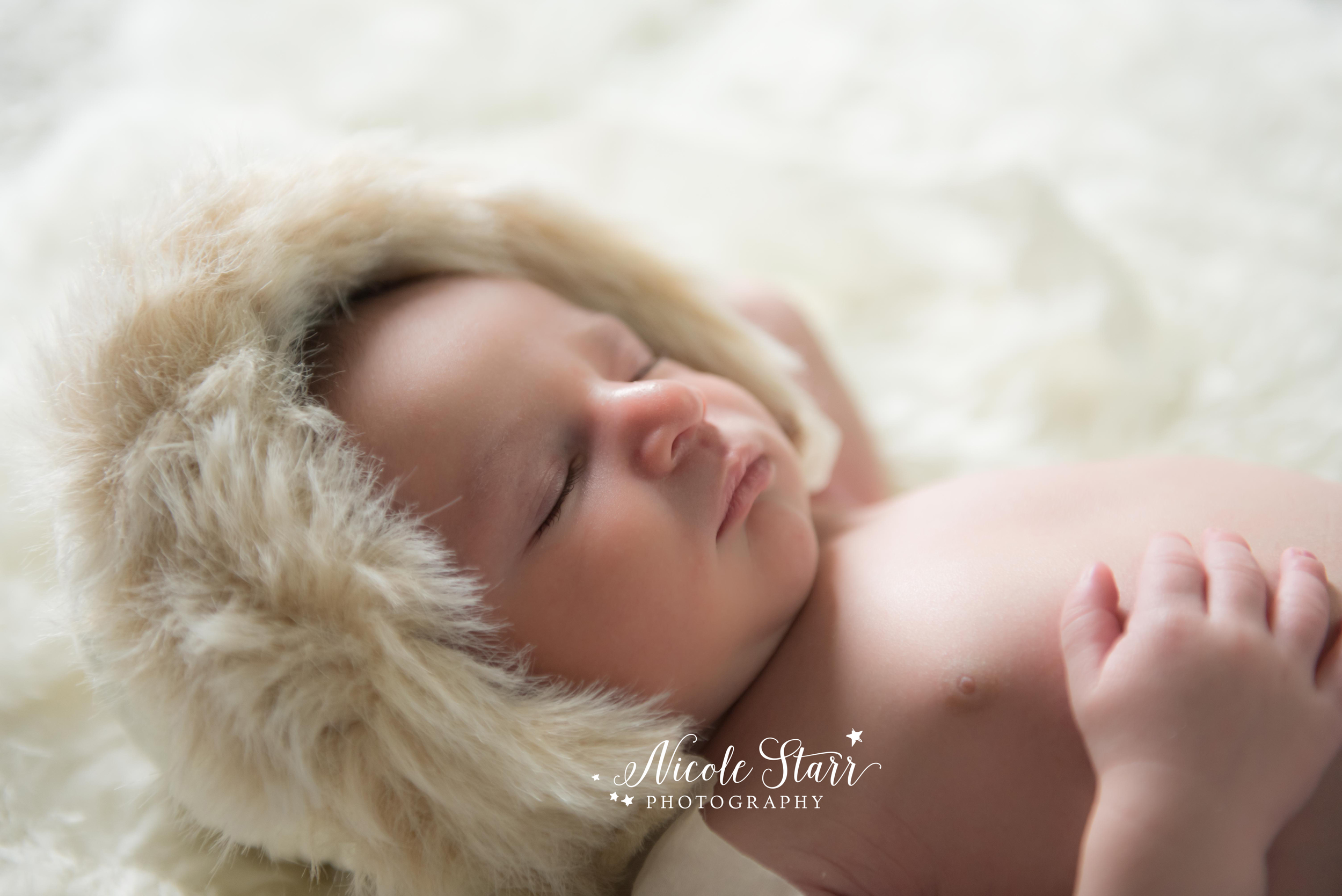 newborn baby boy with fur hat and flokati rug neutral session