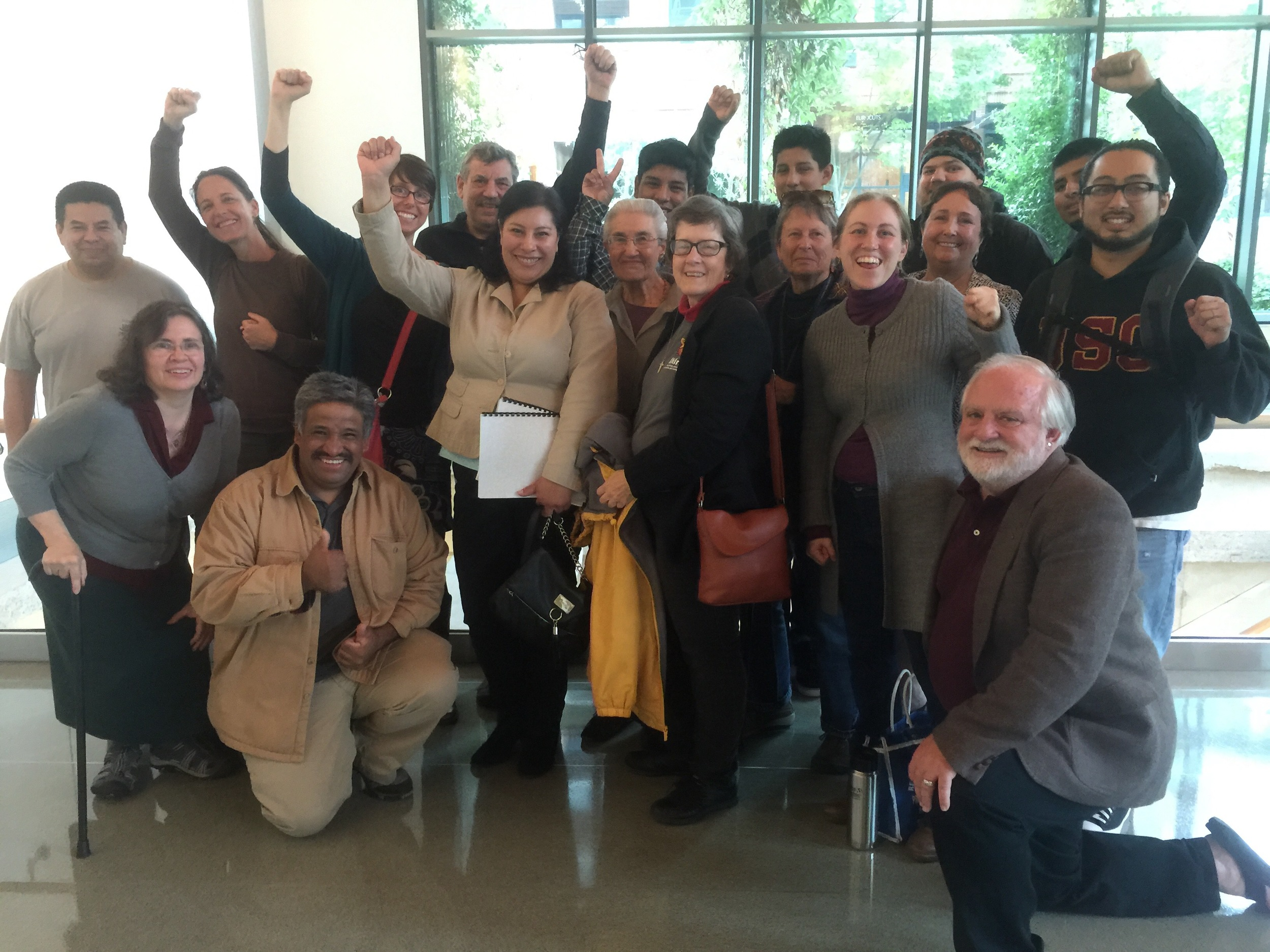 IMIrJ volunteers celebrating victory after accompanying a community member to his court hearing where the judge ruled in his favor.