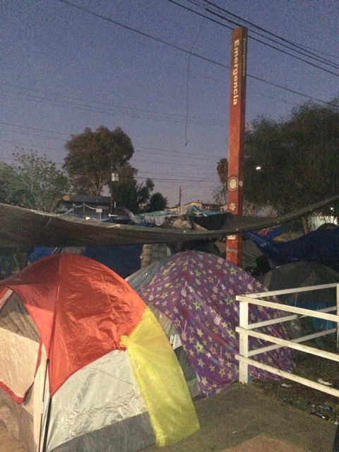 Hundreds of migrants spend the night in tents lining the street outside the Benito Juarez stadium in Tijuana.