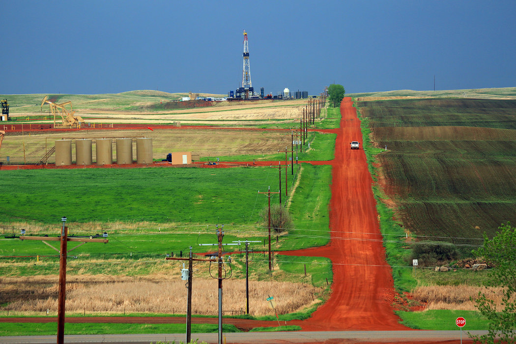 Oil rigs and freshly graded roads near the Fort Berthold Reservation boundary. The reservation sits atop a particularly sweet spot of the Bakken shale formation. (Credit: Jim Wilson/The New York Times )