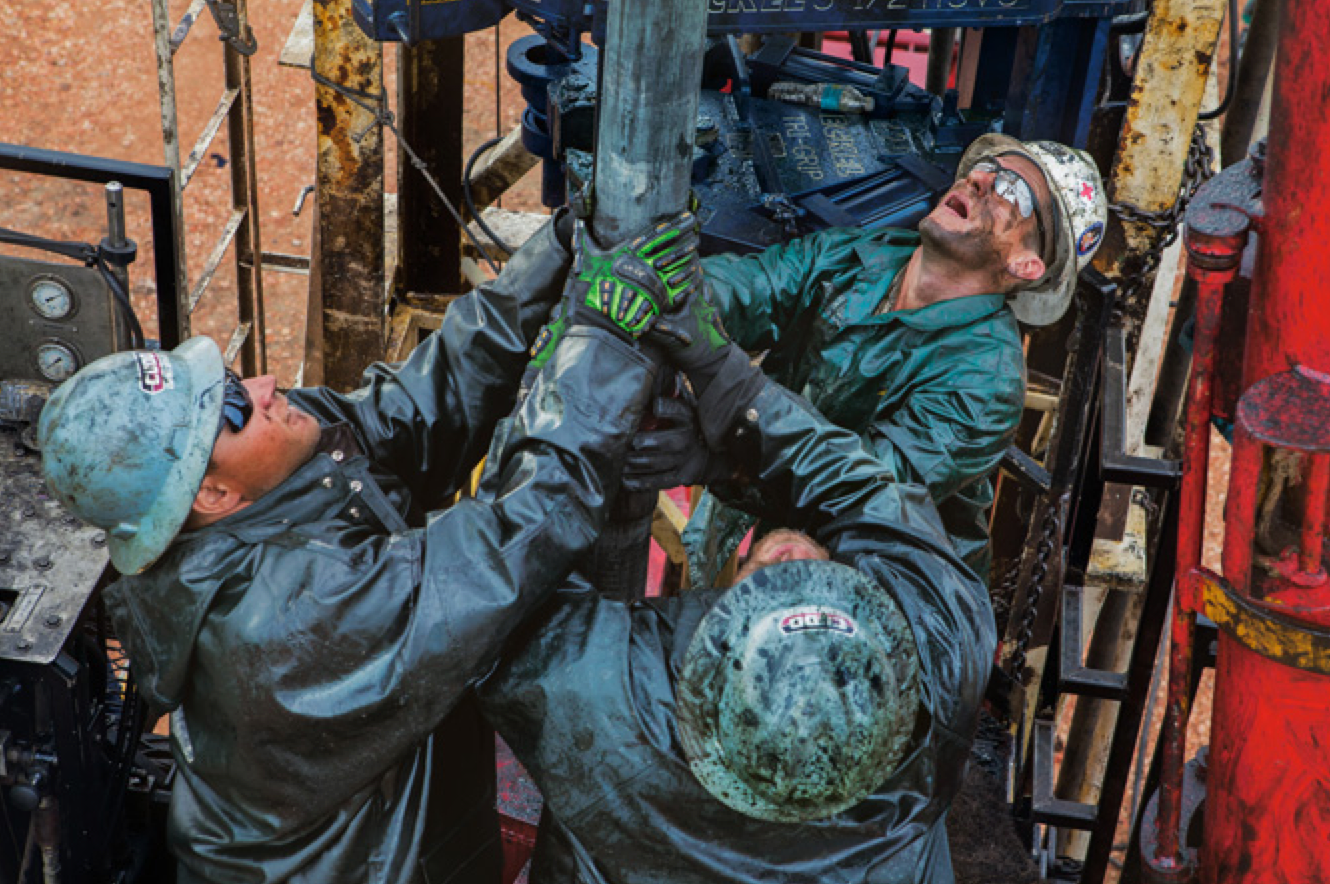 Roughnecks removing two miles of heavy steel drilling pipe one 32-foot section at a time. (Credit:  Eugene Richards )