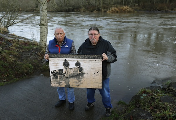 Nisqually Elder Billy Frank Jr., left, and Quinault tribal leader Ed Johnstone display a photo from the late 1960s of tribal fishermen Frank and Don McCloud on the Nisqually River during the Fish Wars. (Credit: Ted Warren/AP)