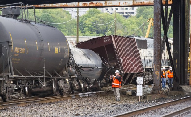 A BNSF investigator photographs the scene where a locomotive and four cars carrying crude oil went off the track beneath the Magnolia Bridge in Seattle's Interbay neighborhood early this morning. (Credit: Mike Siegel / The Seattle Times)